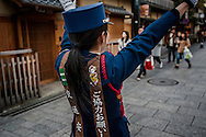 Security guards have been hired in the Gion entertainment and geisha district because foot traffic has expanded to the point that guards have been hired to ensure pedestrians do not stray into the street and get struck by cars.  In the past, security guards were not necessary.  Kyoto, Japan.