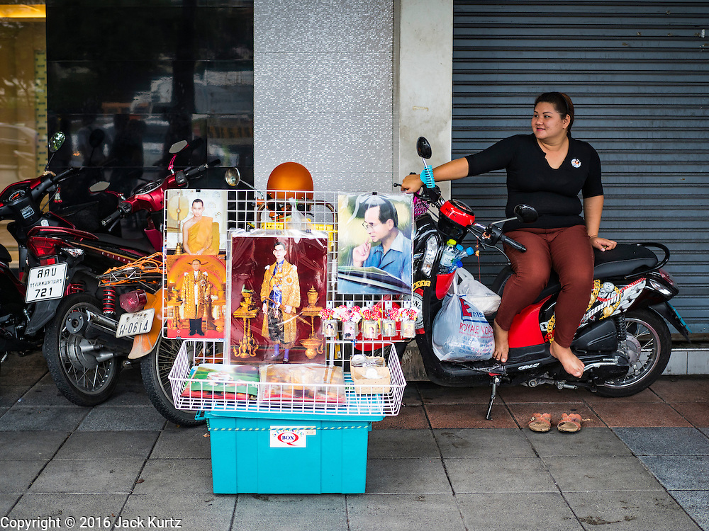 17 OCTOBER 2016 - BANGKOK, THAILAND: A woman sells portraits of Bhumibol Adulyadej, the late King of Thailand, from a table near Sanam Luang in central Bangkok. Thai King Bhumibol Adulyadej died Oct. 13, 2016. He was 88. His death comes after a period of failing health. Bhumibol Adulyadej, was born in Cambridge, MA, on 5 December 1927. He was the ninth monarch of Thailand from the Chakri Dynasty and is also known as Rama IX. He became King on June 9, 1946 and served as King of Thailand for 70 years, 126 days. He was, at the time of his death, the world's longest-serving head of state and the longest-reigning monarch in Thai history.        PHOTO BY JACK KURTZ