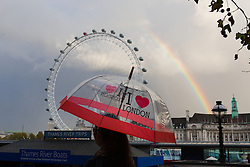 © Licensed to London News Pictures. 10/11/2014. London, UK. A woman walks past the London Eye and a rainbow with umbrella during rain near Westminster Bridge in central London this afternoon. Photo credit : Vickie Flores/LNP