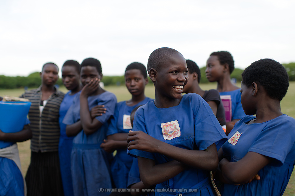 Students laugh during an entertaining drama production dealing with a range of child welfare issues, including child marriages, domestic and sexual abuse, and menstrual hygiene management, at Aputiri Primary School in Eastern Uganda on 31 July 2014 as part of a program sponsored by Plan International.