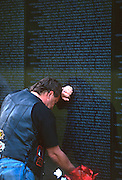 A veteran pauses in memory at the Vietnam Veterans Memorial wall November 11, 1996 in Washington, DC.