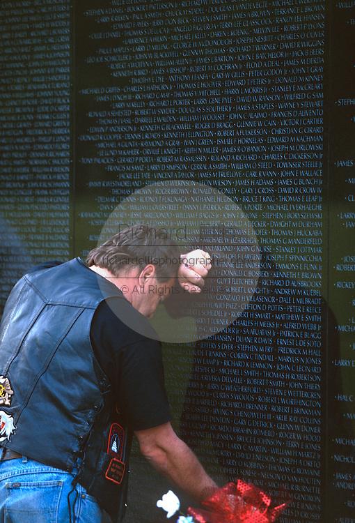 A veteran pauses in memory at the Vietnam Veterans Memorial wall November 11, 1996 in Washington, DC.