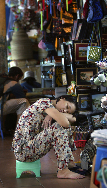 A young clerk falls asleep in frint of her booth at a Market in Hanoi, Vietnam.