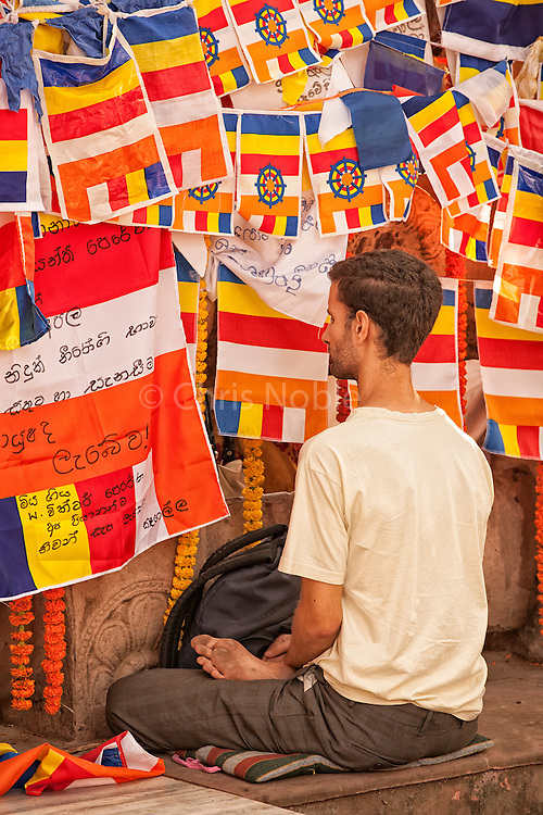 An western visitor meditates at the Mahabodhi Temple, the site of the Buddha's enlightenment, in Bodhgaya India.