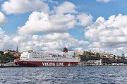 View of Stockholm Sweden waterfront  skyline with Viking Line cruise ship blue sky and cumulus clouds