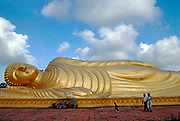 THAILAND; Songkhla.Wat Phr Norn Leam Poh, on Koh Yor, where a huge golden sleeping buddha dominates.A family from Malaysia come to visit.