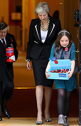 © Licensed to London News Pictures. 25/010/2018. London, UK. Prime Minister Theresa May meets fundraisers Barbara Windsor (93) and Poppy Railton (9) for the Royal British Legion and purchase a poppy to launch the National Poppy Appeal 2018 outside 10 Downing Street. Photo credit: Dinendra Haria/LNP