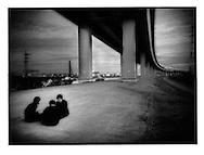 Conspiratorial schoolboys underneath expressway, Shin Koiwa, Chiba, Japan.