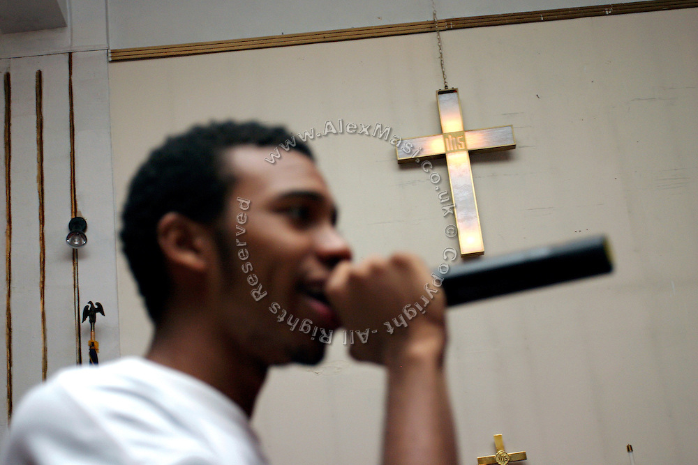 Donovan, 17, a member of the Hells Most Wanted, a Christian Hip Hop group, is singing lyrics during a Mass Service at the Hip Hop Church in Harlem, New York, NY., on Thursday, June 22, 2006. A new growing phenomenon in the United States, and in particular in its most multiethnic city, New York, the Hip Hop Church is the meeting point between Hip Hop and Christianity, a place where ëGodí is worshipped not according to religious dogmatisms and rules, but where the ëHoly Spirití is celebrated by the community through young, unique, passionate Hip Hop lyrics. Its mission is to present the Christian Gospel in a setting that appeals to both, those individuals who are confessed Christians, as well as those who are not regularly attending traditional Services, while helping many youngsters from underprivileged neighbourhoods to feel part of a community, to make them feel loved and to help them not to give up when problems arise. The Hip Hop Church is not only forward-thinking but it also has an important impact where life at times can be difficult and deceiving, and where young people can be easily influenced for the worst purposes. At the Hip Hop Church, members are encouraged to sing, dance and express themselves in any way that the ëSpirit of Godí moves them. Honours to students who have overcome adversity, community leaders, church leaders and some of the unsung pioneers of Hip Hop are common at this Church. Here, Hip Hop is the culture, while Jesus is the centre. Services are being mainly in Harlem, where many African Americans live; although the Hip Hop Church is not exclusive and people from any ethnic group are happily accepted and involved with as much enthusiasm. Rev. Ferguson, one of its pioneer founders, has developed ëHip-Hop Homileticsí, a preaching and worship technique designed to reach the children in their language and highlight their sensibilities, while bringing forth Christianity. This ëKeep It Realí evangelism style is the centrepiece of Rev. Fergusoní