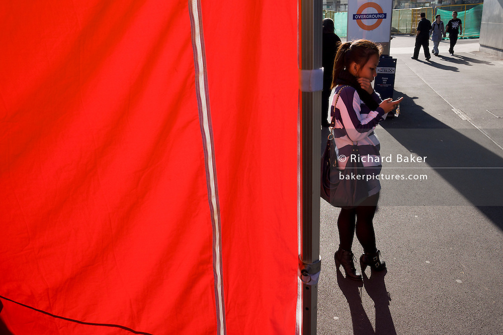 Red cafe screen and local commuting Londoner using a smartphone outside Stratford station, near the 2012 Olympic site.
