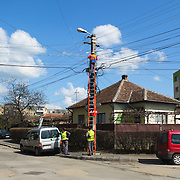 TIMISOARA, ROMANIA - APRIL 21:  Engineers work at telephone lines in the city centre on April 21, 2013 in Timisoara, Romania.  Romania has abandoned a target deadline of 2015 to switch to the single European currency and will now submit to the European Commission a programme on progress towards the adoption of the Euro, which for the first time will not have a target date. (Photo by Marco Secchi/Getty Images)
