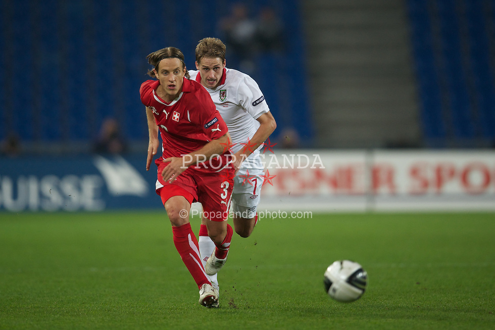 BASEL, SWITZERLAND - Tuesday, October 12, 2010: Wales' David Edwards and Switzerland's Reto Ziegler during the UEFA Euro 2012 qualifying Group G match at St. Jakob-Park. (Pic by David Rawcliffe/Propaganda)