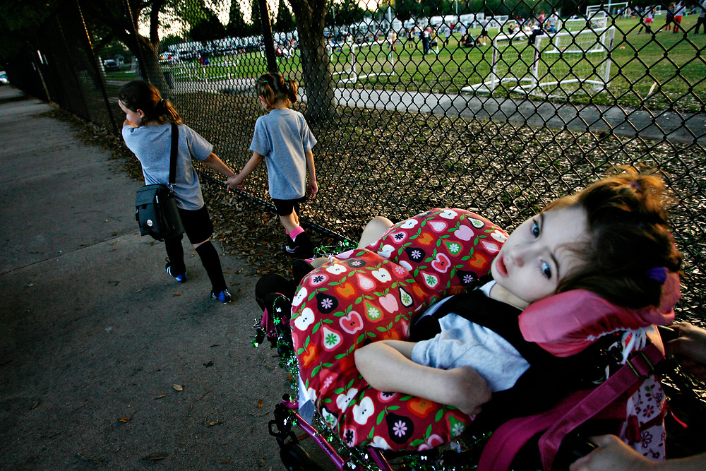 MELISSA LYTTLE   |   Times<br /> SP_351237_LYTT_TWINS_1 (March 16, 2012, Clearwater, Fla.)  Olivia Scheinman, 7, is wheeled back to the family's minivan by her mom, while her twin sister Hailey, right, and Hailey's best friend Ainsley Walling, 7, hold hands after their soccer game, walking and talking a mile-a-minute about all the fun they're going to have during their sleepover that night.  [MELISSA LYTTLE, Times]