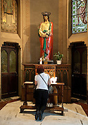 A pilgrim prays in front of a statue of Jesus in Rome. (Sam Lucero photo)