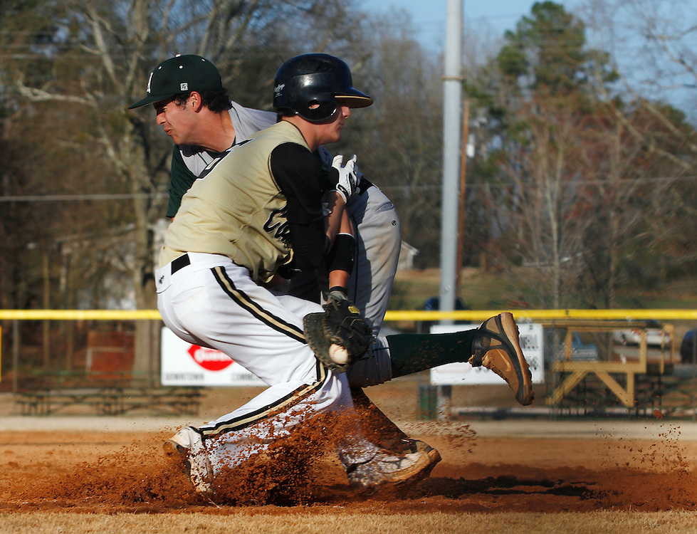 Commerce's Carl Allen collides with Athens Academy's 1st baseman Thomas Sanders after a ground ball hit as the Commerce Tigers take on the Athens Academy Spartans on Tuesday, March 16, 2010 at Commerce High School.  .
