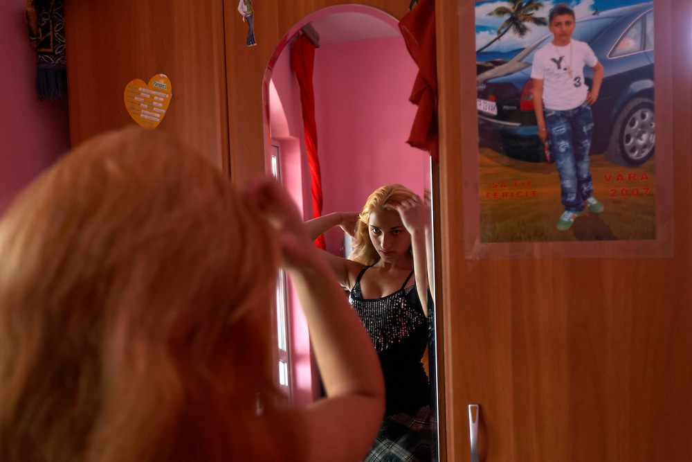 Cassi (13) gets ready to go out with her husband (15) seen on the poster in Buzescu, Romania. Cassi lives with Sami's family and does a lot of the house chores and cooks for the family. Sami still goes to school and wishes to continue but his parents want him to finish the year and start working in the cazan business like his dad.