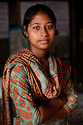 """Nusrat Jahan Popy (16) sits for a portrait in the meeting hut of a Children's Group in Bhashantek Basti (Slum) in Zon H, Dhaka, Bangladesh on 23rd September 2011. Popy says, """"I feel helpless, not angry (if my parents would try to marry me off). I can do stitching and we want to be allowed to work so that we can earn money to support ourselves in our studies and to rid ourselves of poverty and gain independence."""" The Bhashantek Basti Childrens Group is run by children for children with the facilitation of PLAN Bangladesh and other partner NGOs. Slum children from ages 8 to 17 run the group within their own communities to protect vulnerable children from child related issues such as child marriage. Photo by Suzanne Lee for The Guardian"""
