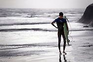 Surfer carrying surfboard coming out of the ocean at Terramar Beach in Carlsbad, CA.