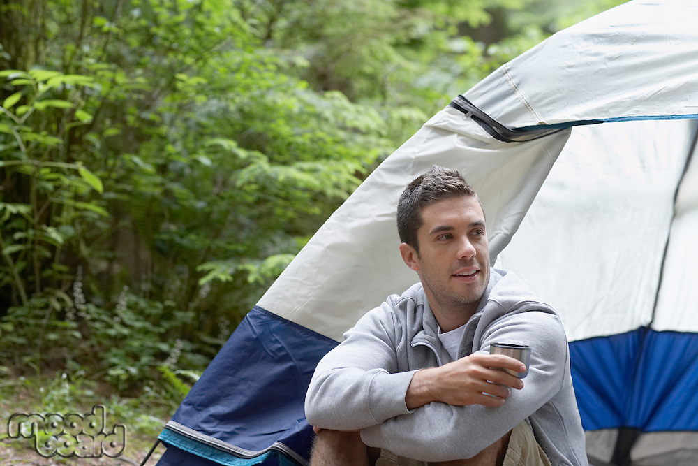Man with drink sitting by tent