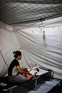 A mother looks over her severely dehydrated child in the medical tent for evacuees in the city's largest stadium in Zamboanga, Mindanao, The Philippines on November 4, 2013. These Internally Displaced People (IDP) had taken refuge in this stadium after surviving the 3 week long attack by MNLF rebels. Photo by Suzanne Lee for SPRINT-IPPF