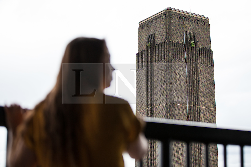 © Licensed to London News Pictures. 14/06/2016. London, UK. A woman looks towards the chimney of the Tate Modern from the viewing platform of the Switch House, the new Tate Modern building which opens to the public on Friday 17 June 2016. The ten-storey extension was designed by architects Herzog & de Meuron and includes the world's first gallery space dedicated exclusively to live art, film and installations. Photo credit: Rob Pinney/LNP