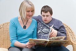 Mother and teenage with Downs Syndrome son reading,