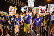 "23 JUNE 2012 - PHOENIX, AZ:  Unitarians keep the crowd back from the jail during a protest against the Maricopa County Jail in Phoenix Saturday. About 2,000 members of the Unitarian Universalist Church, in Phoenix for their national convention, picketed the entrances to the Maricopa County Jail and ""Tent City"" Saturday night. They were opposed to the treatment of prisoners in the jail, many of whom are not convicted and are awaiting trial, and Maricopa County Sheriff Joe Arpaio's stand on illegal immigration. The protesters carried candles and sang hymns.     PHOTO BY JACK KURTZ"