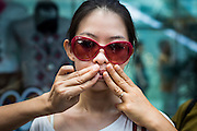 "01 JUNE 2014 - BANGKOK, THAILAND: A woman protests the loss of free speech with the help of her friends, who covered her mouth, during a protest against the Thai military coup at Terminal 21, a popular Bangkok shopping mall. The Thai army seized power in a coup that unseated a democratically elected government on May 22. Since then there have been sporadic protests against the coup. The protests Sunday were the largest in several days and seemed to be spontaneous ""flash mobs"" that appeared at shopping centers in Bangkok and then broke up when soldiers arrived. Protest against the coup is illegal and the junta has threatened to arrest anyone who protests the coup. There was a massive security operation in Bangkok Sunday that shut down several shopping areas to prevent the protests but protestors went to malls that had no military presence.    PHOTO BY JACK KURTZ"