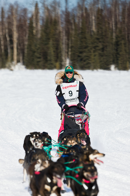Musher Zoya DeNure competing in the 39th Iditarod Trail Sled Dog Race on Long Lake after leaving the Willow Lake area at the restart in Southcentral Alaska.  Afternoon.