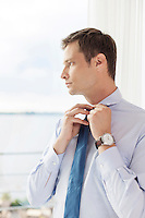 Thoughtful businessman adjusting necktie in hotel