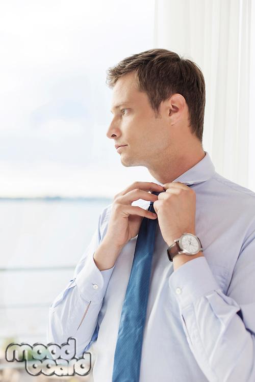 Thoughtful businessman adjusting necktie in hotel