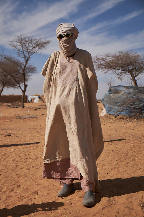 A man stands with head and face covered at a camp of internally displaced people near the village of Kouble by the side of the road on the highway outside of Diffa, Niger on February 17, 2016. The camp is made up of displaced people and refugees from villages along the border between Niger and Nigeria and who fled attacks from Boko Haram. Many of those who fled were farmers along the nearby border. The men will return during the day to tend fields in their villages that have not been burnt or pillaged by Boko Haram.