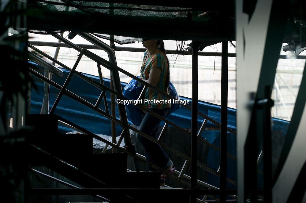 GUANGZHOU, 3. Mai , 2010:.eine Haendelerin geht die Treppe am Tangqi Handelszentrum  in Guangzhou rauf...