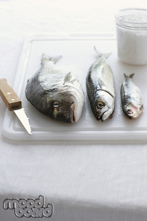 Three fishes on chopping board close-up