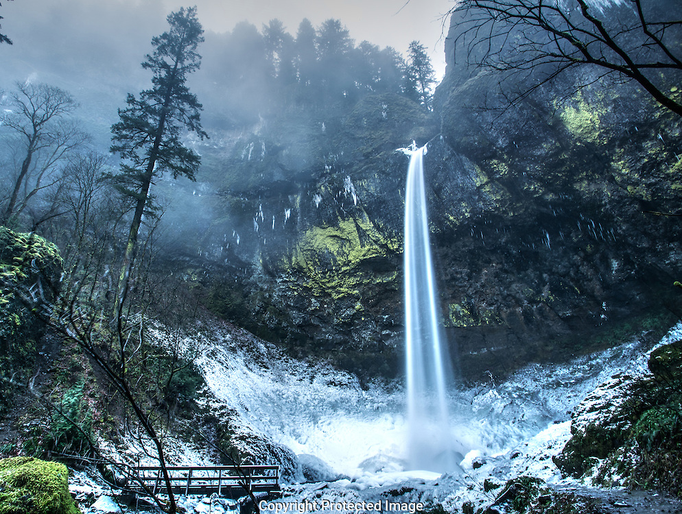 Water turns to ice as it hits the frozen ground at the Columbia Gorge's Elowah Falls in the middle of a cold winter dawn