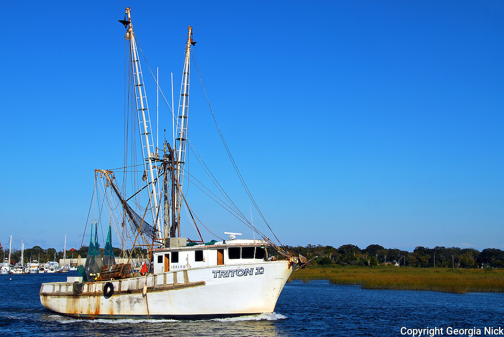 Shrimp boat with arms raised on its way to the Atlanic cruising down the San Sebastain river in St. Augustine, Florida.