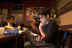 Stanford after dark. Stanford freshman, Salman Karim writing paper  at CoHo with study group.
