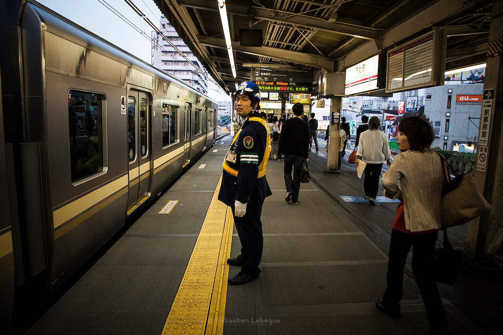 TOKYO, JAPAN, 28 APRIL - ShimoKitaZawa- Man with uniform, helmet, and yellow saftety vest in front of the train with yellow stripe - APRIL 2012 [FR] un homme en uniforme, casque et veste de securite jaune est en face d'un train aux bandes jaunes