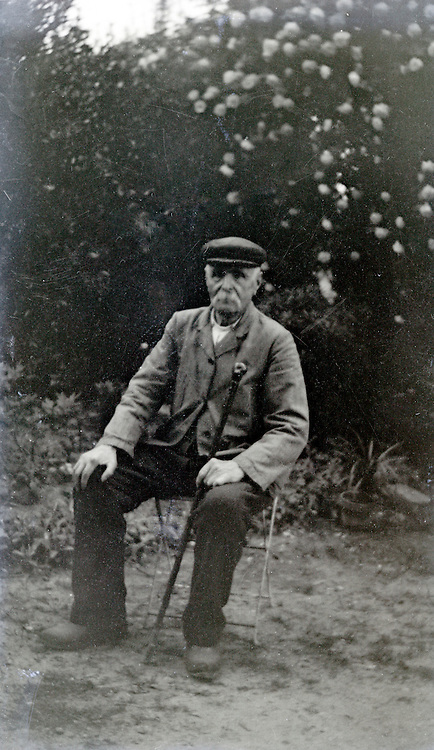 elderly man in workers clothing sitting 1920s