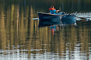 A boy rows a rowboat on  Takhlakh Lake in the Gifford Pinchot National Park, WA state, USA