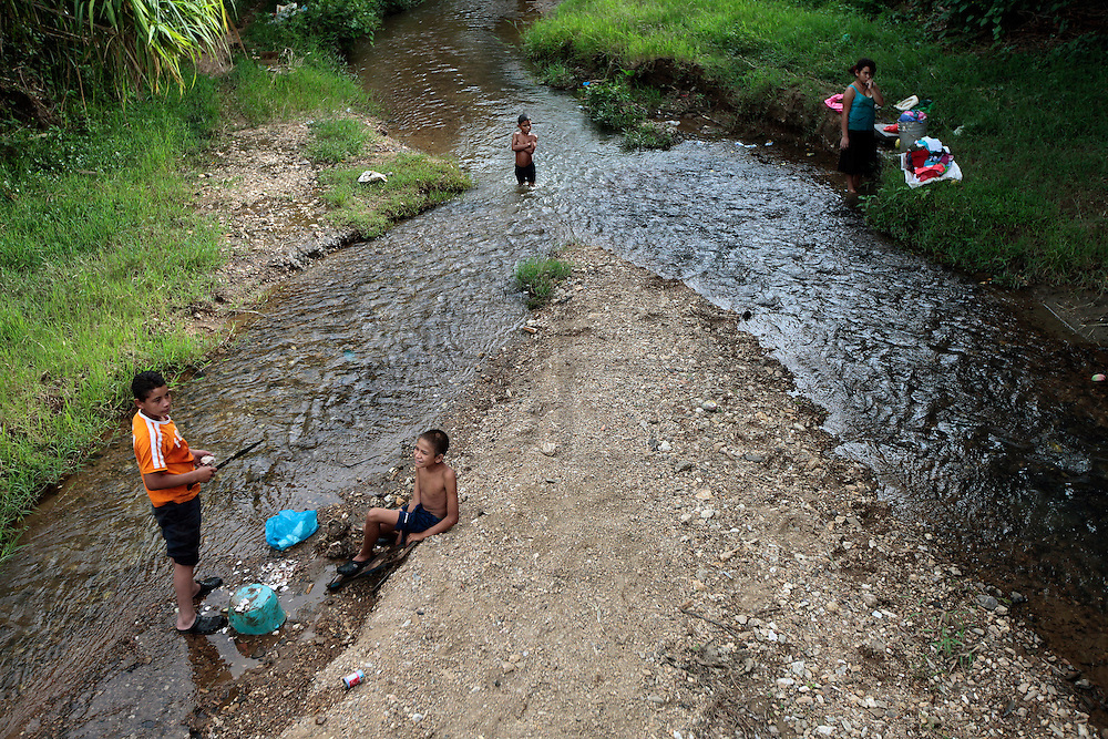 Youngsters play on a stream in Guaimaca, Honduras.  The stream is very poluted, but since its the only source of water in the area, villagers will bath, wash their clothes here.  Honduras is considered the third poorest country in the Western Hemisphere (Haiti, Nicaragua). With over 50% of the population living below the poverty line and 28% unemployed, Hondurans frequently turn to illegal immigration as a solution to their desperate situation. The Department of Homeland Security has noted an 95% increase in illegal immigrants coming from Honduras between 2000 and 2009, the largest increase of any country.