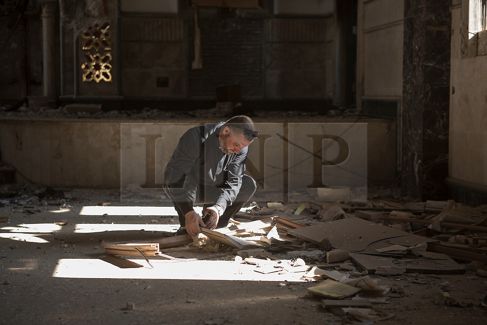 © Licensed to London News Pictures. 04/11/2016. Hamdaniyah, Iraq. Father Ignatius Offy, a Christian priest, examines a damaged religious book in the burnt out shell of the Syriac Catholic Church of Mar Behnam and his sister Mart Sarah in the recently liberated Christian town of Hamdaniyah, Iraq. The church was vandalised and burnt by Islamic State militants during their two year occupation of the town which was retaken by Iraqi Security Forces during the ongoing Mosul Offensive.<br /> <br /> Although located close to a front line, littered with improvised explosive devices and pieces of unexploded ordnance the Christian town of Hamdaniyah has only recently been cleared of ISIS extremists who stayed behind to fight. After the town's liberation as part of the Mosul Offensive residents and priests of the town are now free to take short trips to assess damage, salvage possessions and clear up the mess left by militants during their two year occupation.<br /> <br /> Hamdaniyah, and much of the Nineveh plains, were captured by the Islamic State during a large offensive on the 7th of August 2014 that saw the extremists advance to within 20km of the Iraqi Kurdish capital Erbil. Residents of the town, who included many Christian refugees who escaped there after the fall of Mosul, were then forced to seek sanctuary in the Kurdish areas. In the year and two months of the ISIS occupation churches were burnt, homes were put into use as militant accommodation and bomb factories and some buildings destroyed by coalition airstrikes. Photo credit: Matt Cetti-Roberts/LNP