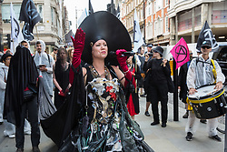 London, UK. 2 July, 2019. Climate change activists from Extinction Rebellion Art and Culture walk along South Molton Street during a silent procession visiting the offices of five major oil companies - ENI, CNPC, Saudi Aramco, Repsol and BP - to declare them a crime scene.