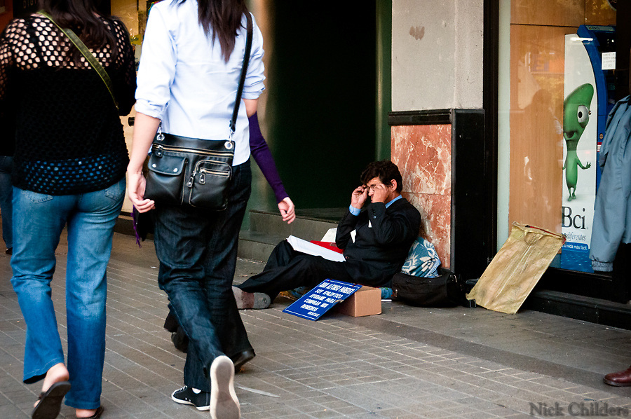 Santiago, Chile 2010<br /> <br /> A man in a suit panders for money in the Los Leones district two weeks after the 7.7 earthquake that struck just outside the capital of Santiago.