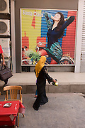 A traditionally-dressed woman walks under a poster for stylish arabic clothing in the modern city of Luxor, Nile Valley, Egypt.