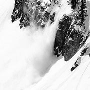 Snow slough blows over the cliff boundaries of the East Face of No Name Peak.