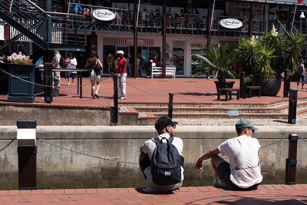 Mossel Bay, South Africa -- January 9, 2018 -- Two young men sitting down by the docks of a shopping mall. Editorial Use Only.