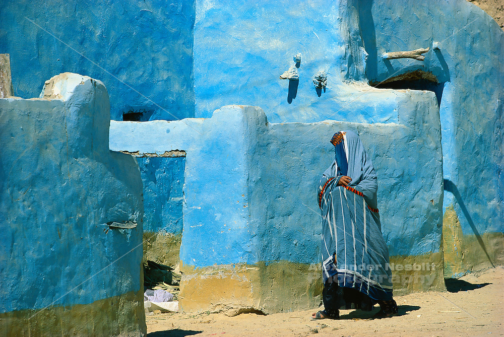 Egypt, Siwa Oasis 1999 - A woman, wrapped in the traditional blue robes of the Siwa Oasis, enters her family home. In her blue robe she blends in perfectly with the surrounding buildings.