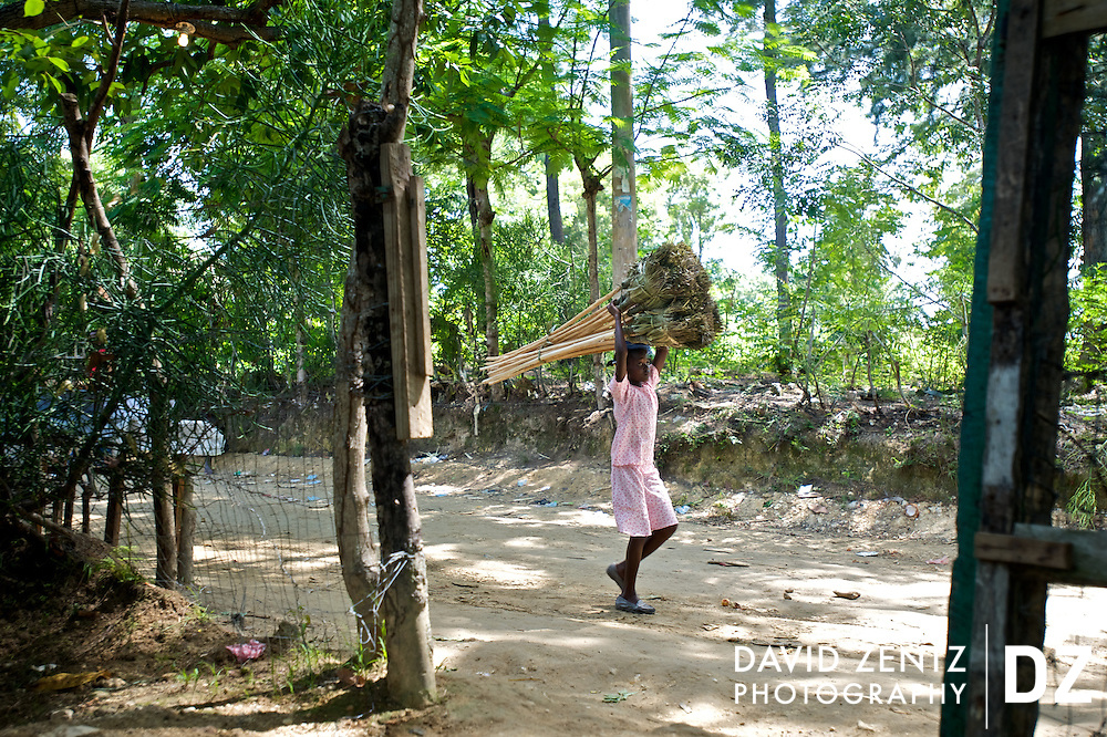 A young girl carries a bundle of straw brooms down a dirt road in the remote village of Ville Bonheur, Haiti on July 16, 2008.