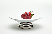 Luscious, red strawberry on a plate with a white background.